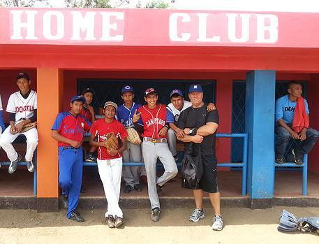 Coach Abrams handing out baseball gear to youth in South America.